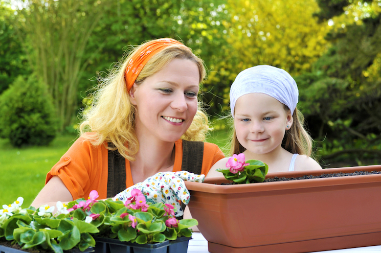 mother and daughter planting in container